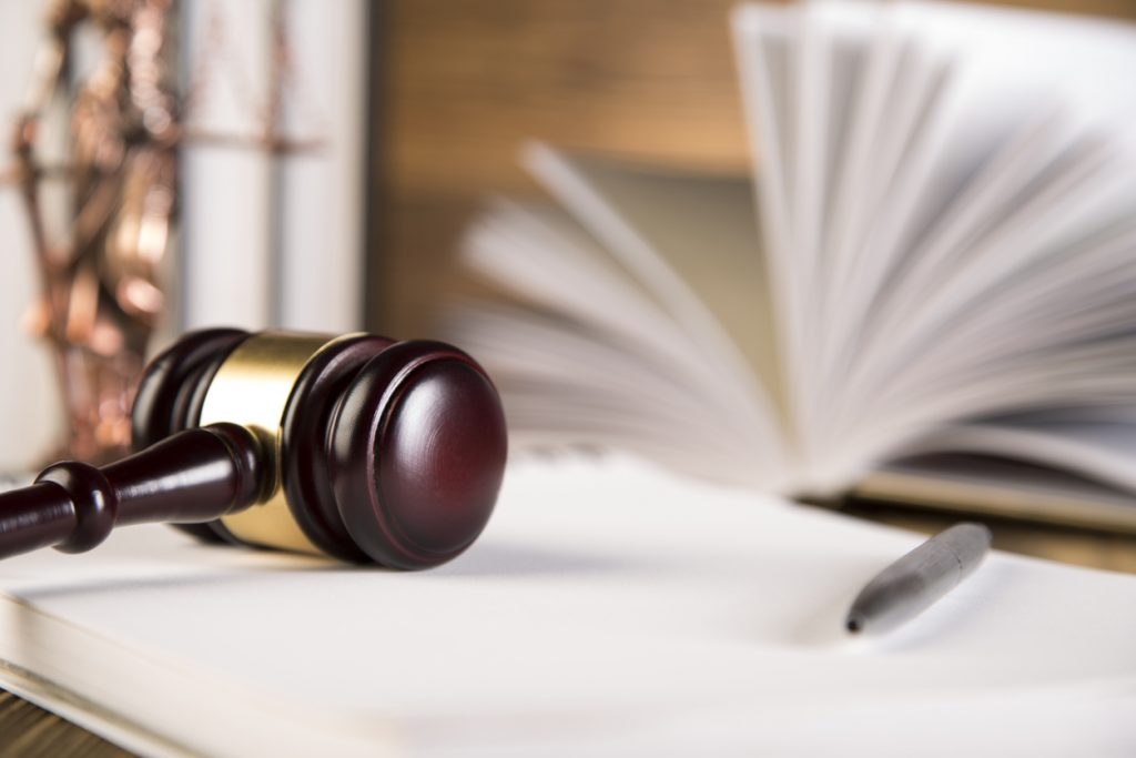Lady of justice, wooden & gold gavel and books on wooden table and wooden background